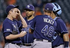 Tampa Bay Rays starting pitcher Jeremy Hellickson, left, rubs sweat from his forehead as he speaks with first baseman James Loney, second from left, pitching coach Jim Hickey and catcher Jose Molina after Baltimore Orioles' J.J. Hardy singled in the first inning of a baseball game, Thursday, Aug. 28, 2014, in Baltimore. (AP Photo/Patrick Semansky)