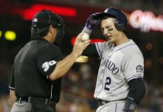 Colorado Rockies' Troy Tulowitzki (2) talks with home plate umpire Rob Drake after striking out during the eighth inning of a baseball game against the Washington Nationals at Nationals Park, Wednesday, July 2, 2014, in Washington. The Nationals won 4-3. (AP Photo/Alex Brandon)