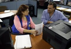 In this Thursday, Feb. 6, 2014 photo, Rose Capote-Marcus, left, helps Waldemar Vega, 50, with problems he is having receiving his unemployment benefits at WorkForce One, in Davie, Fla. On Thursday, Feb. 13, 2014, the Labor Department reports on the number of people who applied for U.S. unemployment benefits a week earlier. (AP Photo/Lynne Sladky)
