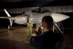 A Canadian Forces pilot has his picture taken in front of a F-35 Strike Fighter prior to an announcement in Ottawa, Friday July 16, 2010. Royal Canadian Air Force fighter pilots of the future could spend almost as much time in a simulator as they do the cockpit under a proposed training regime that has its eyes on the bottom line as much as technology.THE CANADIAN PRESS/Adrian Wyld