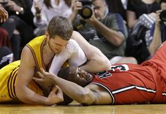 Cleveland Cavaliers center Tyler Zeller, left, and Miami Heat guard Dwyane Wade battle for a loose ball during the first half of an NBA basketball game, Sunday, Feb. 24, 2013, in Miami. (AP Photo/Wilfredo Lee)