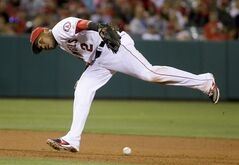 Los Angeles Angels shortstop Erick Aybar can't field a base hit by Toronto Blue Jays' Jose Reyes during the eighth inning of a baseball game in Anaheim, Calif., Monday, July 7, 2014. (AP Photo/Chris Carlson)