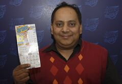 This undated photo provided by the Illinois Lottery shows Urooj Khan, 46, of Chicago's West Rogers Park neighborhood, posing with a winning lottery ticket. The Cook County medical examiner said Monday, Jan. 7, 2013, that Khan was fatally poisoned with cyanide July 20, 2012, a day after he collected nearly $425,000 in lottery winnings. (AP Photo/Illinois Lottery)