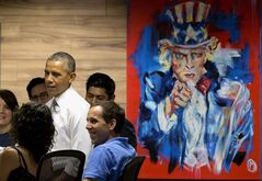 President Barack Obama stands next to a painting of