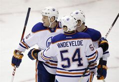 Edmonton Oilers' Ben Eager (55) is congratulated by Chris Vande Velde (54) and Lennart Petrell, rear, following Eager's goal against the Dallas Stars in the third period of an NHL hockey game on Thursday, Feb. 28, 2013, in Dallas. The score was Eager's first of the season in the 5-1 Oilers win. (AP Photo/Tony Gutierrez)
