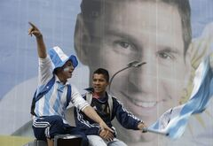 Argentina soccer fans cheer in front of a large portrait of Lionel Messi before the start of the Brazil World Cup final match between Argentina and Germany, on an outdoor screen set up in Buenos Aires, Argentina, Sunday, July 13, 2014. (AP Photo/Jorge Saenz)