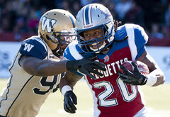 Montreal Alouettes' Victor Anderson (20) is tackled by Winnipeg Blue Bombers' Alex Hall (96) during first half CFL football action in Montreal, Monday. The Bombers won 27-22.