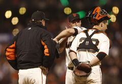 San Francisco Giants pitcher George Kontos, center, receives a visit on the mound from catcher Buster Posey, right, and pitching coach Dave Righetti during the seventh inning of a baseball game against the Washington Nationals, Monday, June 9, 2014, in San Francisco. (AP Photo/Beck Diefenbach)