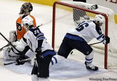 Winnipeg Jets' Andrew Ladd, right, scores the game-winning goal past Philadelphia Flyers goalie Ilya Bryzgalov during the third period of an NHL hockey game Thursday in Philadelphia. The Jets won 9-8.