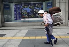 A woman walks by an electronic stock board of a securities firm in Tokyo, Friday, July 18, 2014. Tokyo's Nikkei 225, the regional benchmark, tumbled 1.1 percent lower at 15,202.55. (AP Photo/Koji Sasahara)