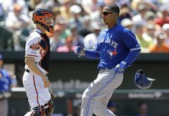 Toronto Blue Jays' Anthony Gose, right, loses his helmet as he scores in front of Baltimore Orioles catcher Nick Hundley on a sacrifice fly hit by Melky Cabrera in the fifth inning of a baseball game on Sunday, June 15, 2014, in Baltimore. (AP Photo/Patrick Semansky)