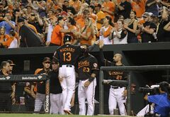 Baltimore Orioles' Manny Machado (13) high-fives teammates in the dugout after scoring on a single by J.J. Hardy in the sixth inning of a baseball game against the Seattle Mariners, Friday, Aug. 1, 2014, in Baltimore. (AP Photo/Patrick Semansky)
