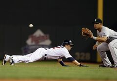 Minnesota Twins' Brian Dozier, left, dives safely back to first as Chicago White Sox first baseman Jose Abreu waits for the throw during a pickoff attempt in the first inning of a baseball game, Thursday, June 19, 2014, in Minneapolis. (AP Photo/Jim Mone)