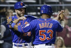 New York Mets' Eric Campbell (29) is greeted at home plate by teammate Bobby Abreu (53) after they scored on a double to center field by Travis d'Arnaud against the Texas Rangers in the eighth inning of a baseball game on Friday, July 4, 2014, in New York. (AP Photo/Julie Jacobson)