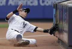 New York Yankees right fielder Ichiro Suzuki slides into a barrier on foul territory while chasing a foul ball by Cincinnati Reds' Neftali Soto during the ninth inning of an MLB baseball game, Saturday, July 19, 2014, at Yankee Stadium in New York. The Yankees won 7-1. (AP Photo/Julio Cortez)