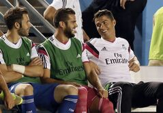 Real Madrid's Cristiano Ronaldo, right, smiles as he talks with teammates on the bench in the first half of a Guinness International Champions Cup soccer tournament match, Tuesday, July 29, 2014, in Dallas. (AP Photo/Tony Gutierrez)