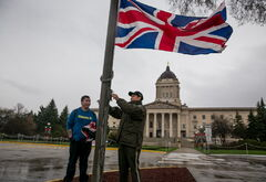 The Union Jack is raised at the Manitoba legislature by protection services officer Eustaquio Tadeo, with help from Tyler MacMartin, for the visit of Prince Charles and his wife Camilla, Duchess of Cornwall.