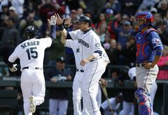 Seattle Mariners' Kyle Seager (15) is greeted by teammates Justin Smoak, center, and Dustin Ackley (obscured) after hitting a three-run go-ahead home run in the eighth inning of a baseball game against the Texas Rangers, Sunday, April 27, 2014, in Seattle. Rangers catcher Robinson Chirinos, right, looks on. (AP Photo/Ted S. Warren)