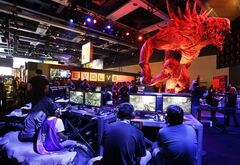 A giant monster looms over gamers playing Evolve, a video game published by 2K Games, which is scheduled to be released in early 2015, Friday, Aug. 29, 2014, at the Penny Arcade Expo, a fan-centric celebration of gaming in Seattle. The event is expected to be attended by roughly 85,000 gamers and will include concerts, game tournaments and previews of upcoming titles. (AP Photo/Ted S. Warren)