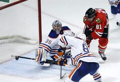 Chicago Blackhawks right wing Marian Hossa (81), of Slovakia, shoots the winning goal past Edmonton Oilers goalie Nikolai Khabibulin (35), of Russia, and center Sam Gagner during overtime of their NHL hockey game, Monday, Feb. 25, 2013, in Chicago. The Blackhawks won 3-2. (AP Photo/Charles Rex Arbogast)