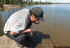 Sam Wood takes a drink from Kalicahoolie Lake, north of Wasagamack. This is traditional hunting and fishing area for the First Nation.