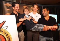 Pro hockey players Nolan Baumgartner (from left), Travis Zajac and Nigel Dawes gave eight­-year-old Dane Hantscher a lift at Believe in the Goal press conference at the MTS Centre Tuesday morning. The pros will be playing in the fifth annual charity game on Aug. 12.