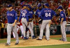 Texas Rangers starting pitcher Matt Harrison, left, leaves the mound in the fifth inning during a baseball game against the Anaheim Angels at Anaheim Stadium in Anaheim, Calif., Saturday, May 3, 2014. (AP Photo/Sandy Huffaker)