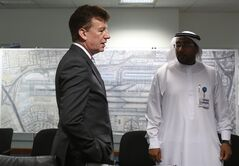 In this June 17, 2014, photo, Dubai Airports CEO Paul Griffiths, left, a 56-year-old Briton, talks with one of his Emirati staff while he is visiting the Joint Control Room which is essentially the nerve center of operations for the airport in Dubai, United Arab Emirates. Now that he's had a taste of running the world's busiest air hub for international passengers, Griffiths is determined to hang on to the honor while setting his sights on an even bigger prize: beating Atlanta for the title of busiest airport on the planet. (AP Photo/Kamran Jebreili)