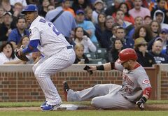 Chicago Cubs third baseman Luis Valbuena, left, looks to first base after forcing out Cincinnati Reds' Skip Schumaker at third base during the fifth inning of a baseball game in Chicago, Wednesday, June 25, 2014. Cincinnati Reds' Mat Latos was safe at first. (AP Photo/Nam Y. Huh)