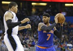 New York Knicks' Carmelo Anthony (7) looks to pass the ball around Orlando Magic's Tobias Harris, left, in the first half of an NBA basketball game in Orlando, Fla., Monday, Dec. 23, 2013. (AP Photo/John Raoux)
