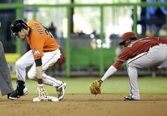 Miami Marlins' Christian Yelich, left, beats the throw to Arizona Diamondbacks shortstop Didi Gregorius, right, as he is safe with a double in the first inning during a baseball game, Sunday, Aug. 17, 2014, in Miami. (AP Photo/Lynne Sladky)
