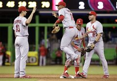 St. Louis Cardinals third baseman Matt Carpenter (13), right fielder Oscar Taveras (18), second baseman Kolten Wong, second from right, and shortstop Jhonny Peralta (27) celebrate after the defeating the Miami Marlins 5-2 during a baseball game, Wednesday, Aug.13, 2014, in Miami. (AP Photo/Lynne Sladky)