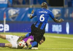 Montreal Impact's Hassoun Camara collides with FC Edmonton's goalkeeper John Smits during second half second leg semi-final Canadian championship soccer action in Montreal, Wednesday, May 14, 2014. THE CANADIAN PRESS/Graham Hughes