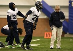 Seattle Seahawks head coach Pete Carroll, right, laughs as running back Marshawn Lynch, left, and fullback Michael Robinson, center, warm up at the start of NFL football practice Thursday, Jan. 30, 2014, in East Rutherford, N.J. The Seahawks and the Denver Broncos are scheduled to play in the Super Bowl XLVIII football game Sunday, Feb. 2, 2014. (AP Photo)