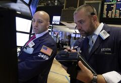 Specialist John Parisi, left, and trader Kevin Lodewick work on the floor of the New York Stock Exchange, Tuesday, Aug. 19, 2014. Better news on home building and corporate earnings are sending stocks higher. (AP Photo/Richard Drew)