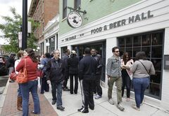 This May 17, 2014 photo shows diners waiting for a table outside The Eagle restaurant in the Over-the-Rhine neighborhood of Cincinnati, a picturesque neighborhood on the edge of downtown that locals simply call OTR. (AP Photo/Al Behrman)
