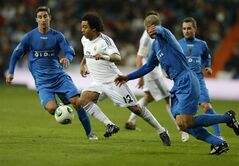 Real's Marcelo, centre takes the ball through the Xativa defence during a round-of-32, 2nd leg Copa del Rey soccer match between Real Madrid and third-division club Xativa Olimpic at the Bernabeu stadium in Madrid, Wednesday, Dec. 18, 2013. (AP Photo/Paul White)
