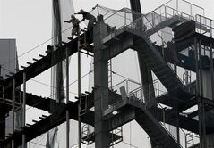 FILE - In this March 1, 2014 file photo, workers reach for the net at a construction site in Tokyo. Japan raised its estimate of January-March quarter economic growth Monday, June 9, 2014 as investment by companies was stronger than first thought. (AP Photo/Shuji Kajiyama, File)
