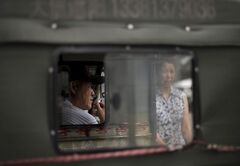 A Chinese man smokes inside his tricycle as he waits for customer outside a shopping mall in Beijing, China Wednesday, July 16, 2014. China's economic growth edged up in the latest quarter and more than 7 million new jobs were created in the first half of the year, easing pressure on communist leaders as they try to prevent a precipitous slowdown in the world's second-largest economy. (AP Photo/Andy Wong)