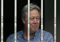 American Chip Starnes, co-owner of Specialty Medical Supplies looks out from a window as he is held hostage by angry workers inside his plant at the Jinyurui Science and Technology Park in Qiao Zi township of Huairou District, on the outskirts of Beijing, China Tuesday, June 25, 2013. Starnes said he's waiting for his lawyers to arrive to resolve a compensation dispute that highlights tensions in China's labor market. (AP Photo/Andy Wong)