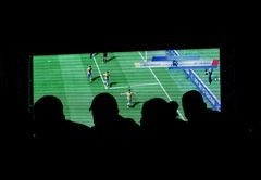 People watch a video game during the FIFA Interactive World Cup 2014 Grand Final at Sugar Loaf, Rio de Janeiro, Brazil, Thursday, July 3, 2014. The FIWC is organised by FIFA and its presenting partners, and is recognized by Guinness World Records as the world's largest online gaming tournament. (AP Photo/Silvia Izquierdo)
