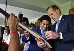 Australian Prime Minister Tony Abbott, signs a cricket bat as India's retired batting maestro Sachin Tendulkar watches during an event to interact with cricket players in Mumbai, India, Thursday, Sept. 4 , 2014. THE CANADIAN PRESS/AP, Rajanish Kakade