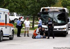 A bus driver talks to onlookers as paramedics tend to a man who was hit by a bus on Jefferson in the Maples.