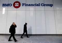 People walk past the Bank of Montreal Financial Group building in downtown Toronto on January 28, 2014. THE CANADIAN PRESS/Nathan Denette