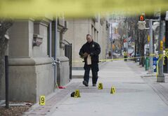 A police officer gathers evidence outside a Main Street nightclub Sunday morning.  Members of the Winnipeg Police Service were on the scene of a homicide outside of Opera Ultralounge on Main Street Sunday morning.