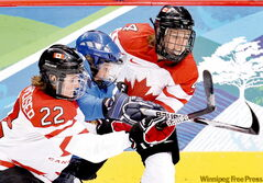 Canada's Hayley Wickenheiser (left) and Becky Kellar team up to outmuscle Finland's Karoliina Rantamaki during women's semifinal Olympic hockey action in Vancouver on Monday. Canada won 5-0 to advance to the gold-medal game against the U.S.