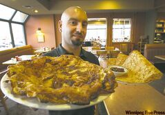 Original Pancake House server Brad Medeiros with giant apple pancake, front, and Swedish pancakes.