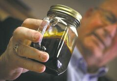 Williston, N.D., Mayor E. Ward Koeser displays a jar containing Bakken crude oil.