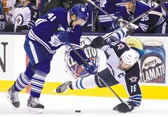 Leafs forward Nikolai Kulemin employs a bit of stickwork to send Jets captain Andrew Ladd flying during second-period action in Toronto.