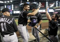 Colorado Rockies' Matt McBride, second from left, celebrates with teammates after hitting a second-inning home run during a baseball game against the Arizona Diamondbacks, Saturday, Aug. 30, 2014, in Phoenix. (AP Photo/Rick Scuteri)